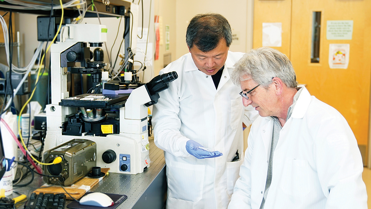 UCI professors Abe Lee and Chris Hughes working together in the Center for Advanced Design and Manufacturing of Integrated Microfluidics (CADMIM) at UCI's Henry Samueli School of Engineering.  Jackie Connor / UCI Beall Applied Innovation