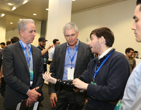 b3aaf7b71b From left, Ken Walsh and Fred Schreiner talk with Stuart Dorff about his  team's Magic Sleeve, a device to help people with vision impairment.