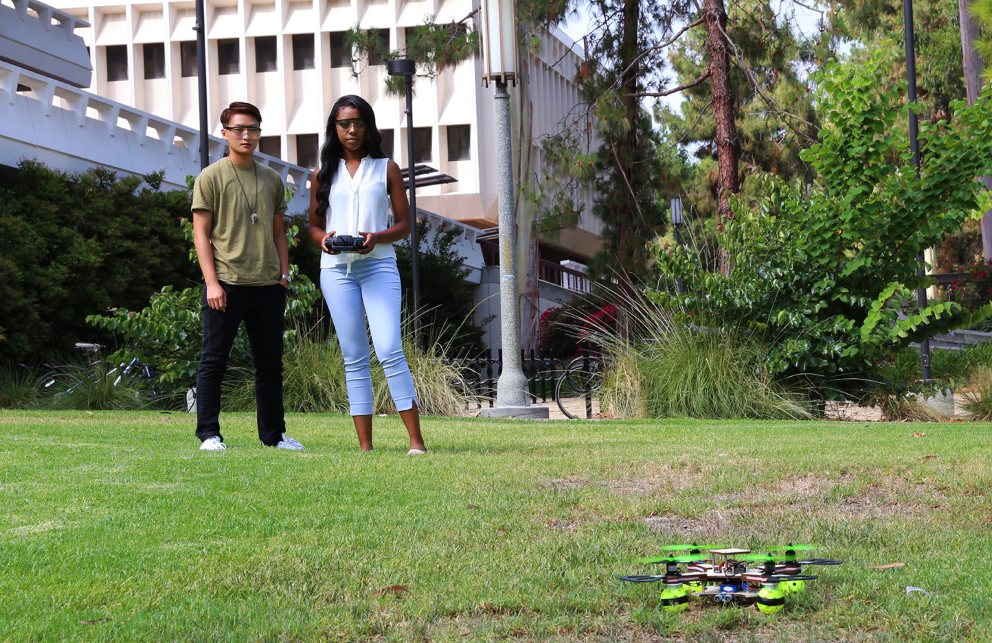 Two UCI students work on drones they built and programmed.