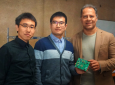 Graduate students Zisong Wang and Huan Wang (from left), along with their adviser, Heydari, display a testing board containing their novel receiver chip.