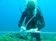 Kristen Davis, UCI assistant professor of Earth system science and civil & environmental engineering attaches a temperature sensor to a fiberoptic cable at the Dongsha Atoll reef.