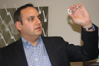 Dr. Arash Kheradvar holds a model of a heart valve used in his research to advance cardiovascular science.