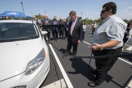 Ronald Fleming, right, executive director of UCI Transportation & Distribution Services, helps U.S. Secretary of Labor Marty Walsh connect an electric car with a campus charging station, with Chancellor Howard Gillman, UC Regent John A. Pérez, UCI Vice Chancellor for Research Pramod Khargonekar, U.S. Rep. Mike Levin and Irvine Mayor Farrah Khan looking on. Steve Zylius / UCI