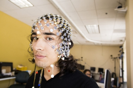 UCI doctoral candidate Sumner Norman wears an EEG cap that figures prominently in his robotics research to help stroke victims. Elena Zhukova / UCOP